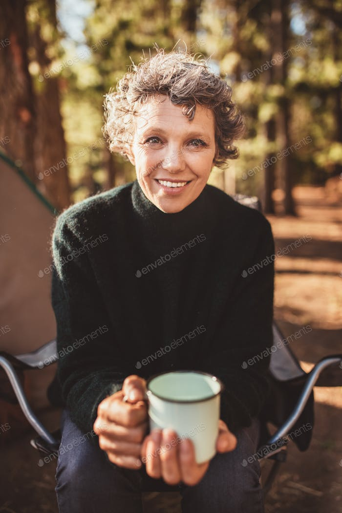 Senior woman sitting outside the tent with a cup of coffee