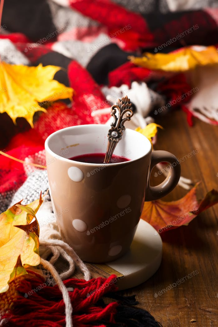 Red tea with autumn leaves on brown wooden background, homemade drink in autumn. Copy space