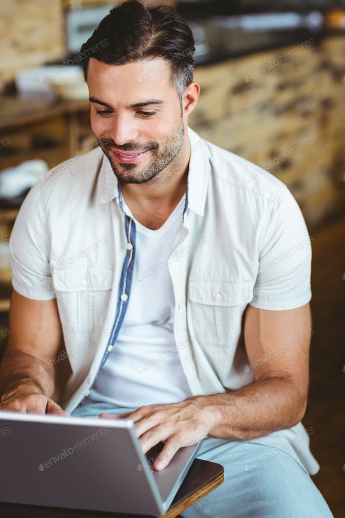 Happy young businessman working at laptop drinking coffee at coffee