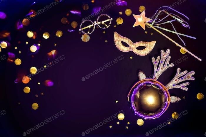 Gold glitzernde Masquerade Accessoires auf schwarzem Hintergrund mit Konfetti