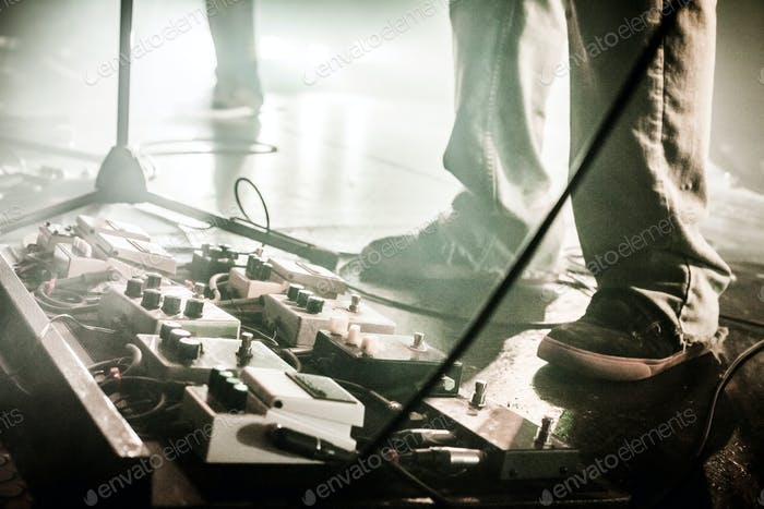 Guitar Pedals on a stage with live band performing during a Show
