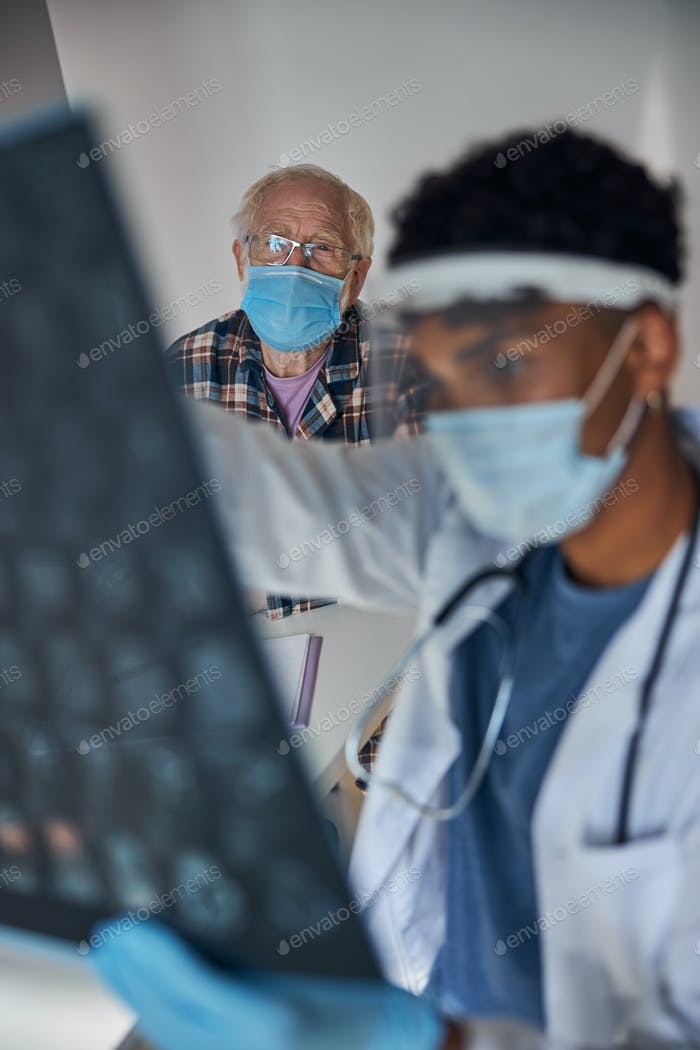 Concentrated young neurologist examining his patient MRI scans