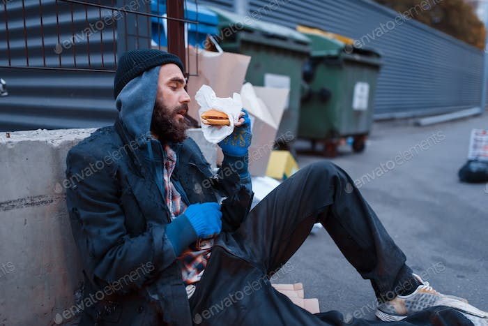 Dirty beggar with food sitting at the trashcan