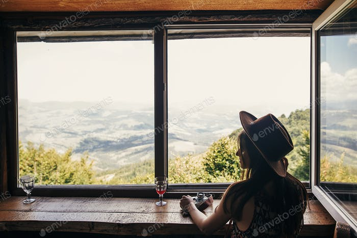 stylish girl traveler ih hat sitting at window in cottage with view on mountains and sky