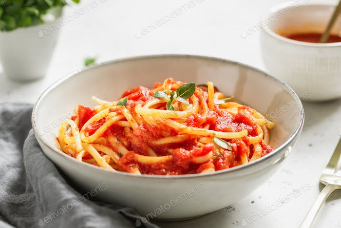 Traditional pasta with tomato and Greek basil sauce in a ceramic bowl on a white table.