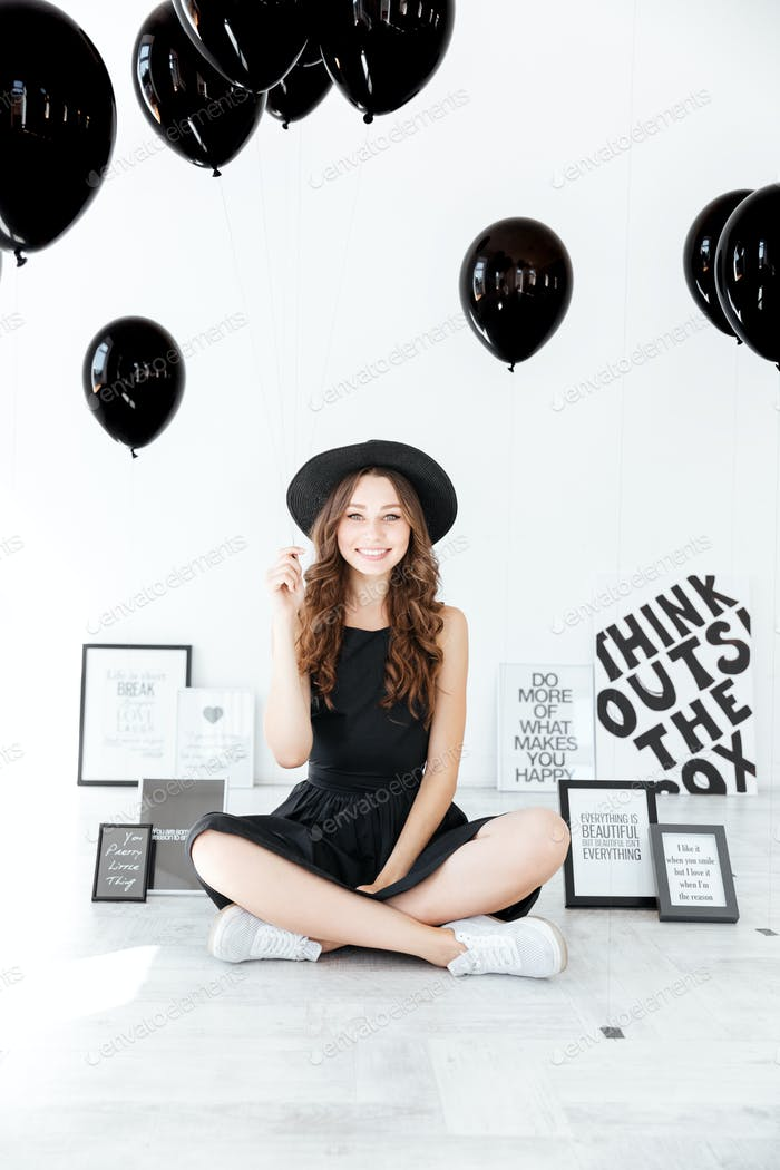 Portrait of happy charming girl with black balloons sitting