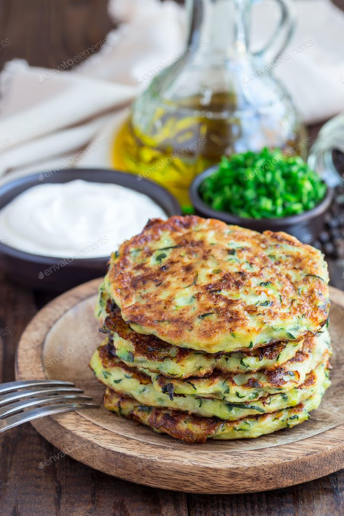 Vegetarian zucchini fritters or pancakes, served with greek yogu