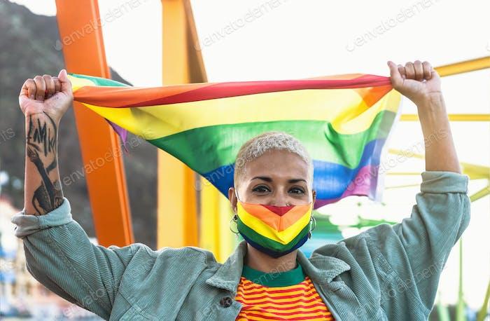 Young woman wearing gay pride mask holding rainbow flag symbol of Lgbtq social movement