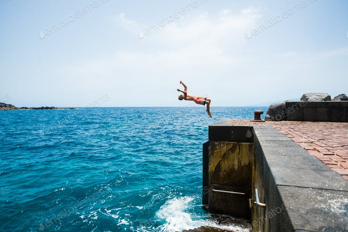 one young man jumping off a cliff doing a backflip to the water - alone fitness and healthy