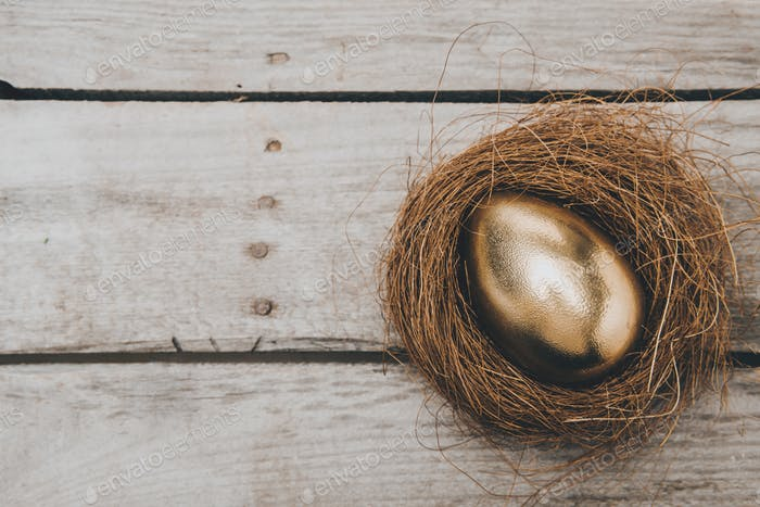 Close-up top view of golden Easter egg in nest on wooden table, Happy Easter concept