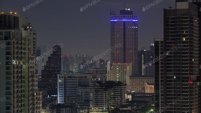 Timelapse of windows lights blinking in night Bangkok, Thailand