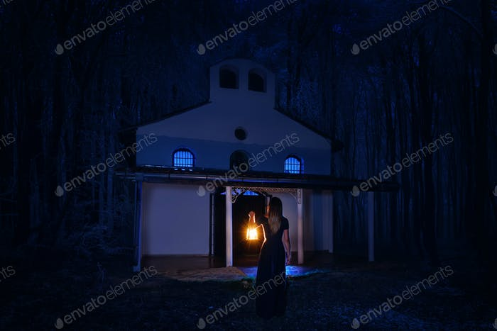 Beautiful girl in long dress with lantern alone in the dark forest