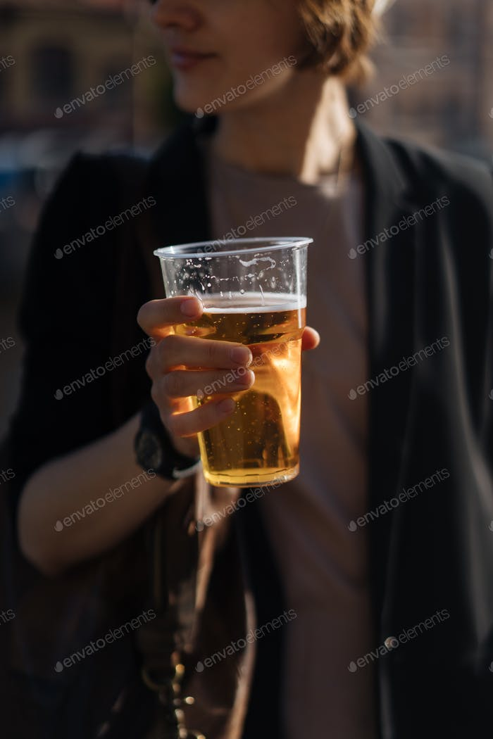 Woman with beer in cup on riverfront