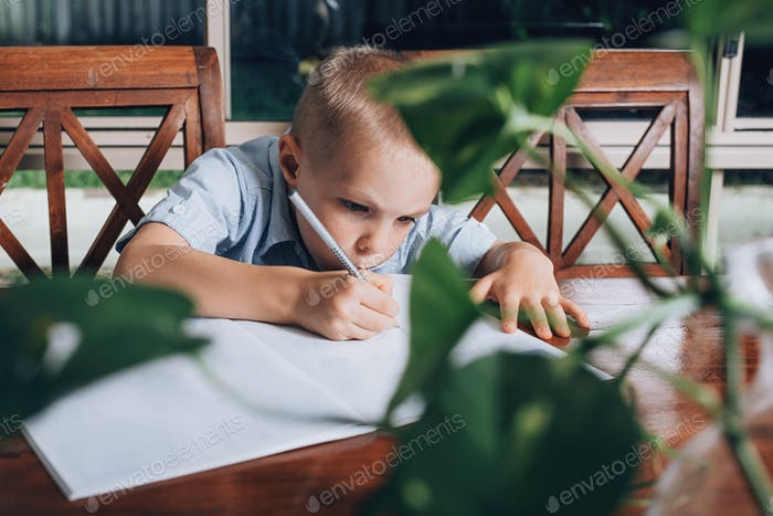 Little child drawing in a textbook at home, a boy holding pen and writing.