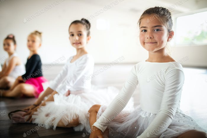Group of fit happy children exercising ballet in studio together