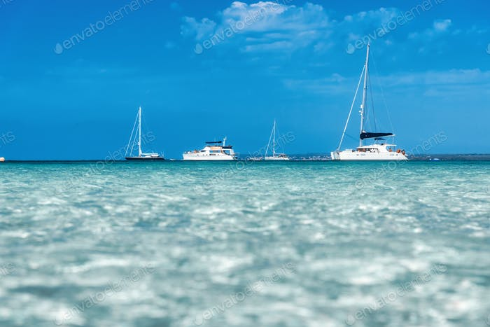 Boats and yachts in transparent sea at sunny bright day