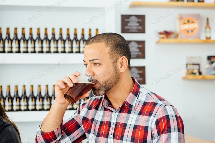 Bearded man tasting dark craft beer