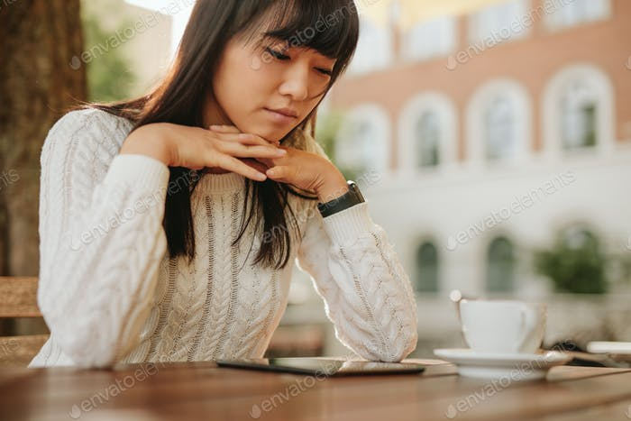 Woman using digital tablet at outdoor coffee shop