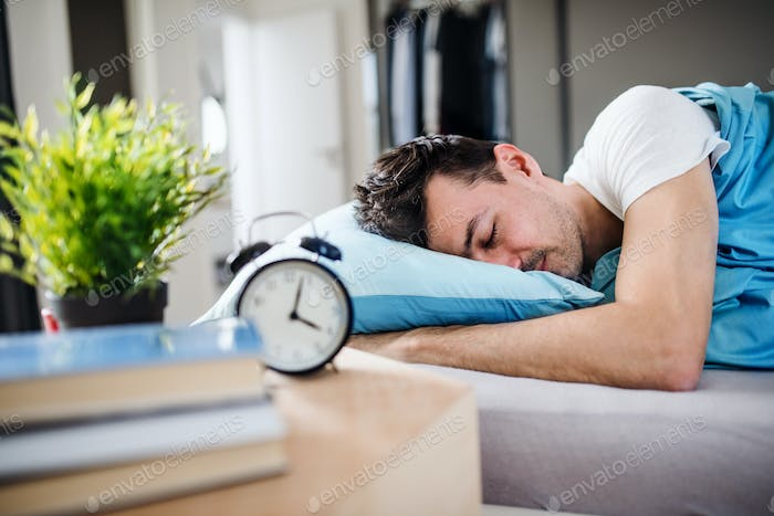 Young man with alarm clock in bed at home, sleeping