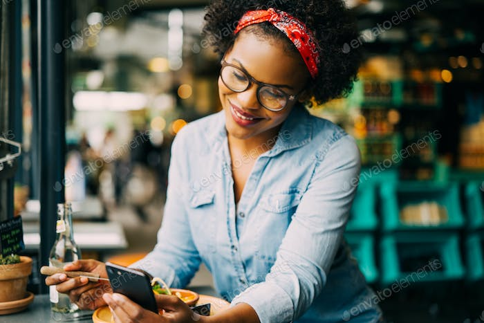 Smiling young woman reading a text message in a cafe