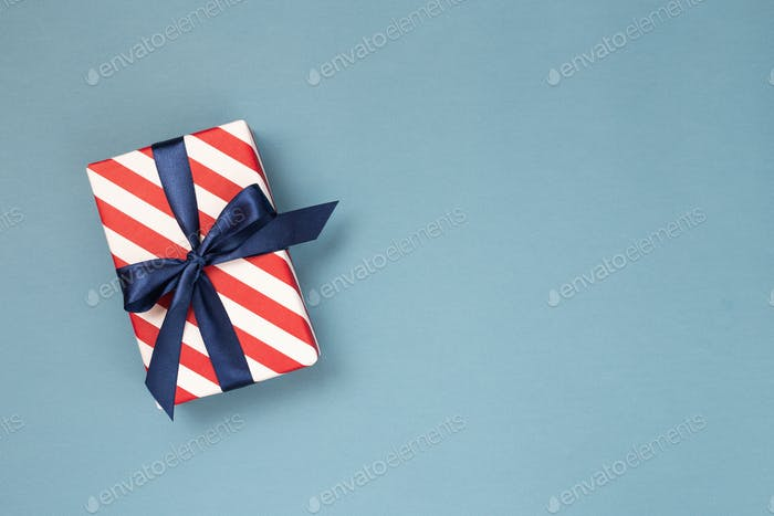 Gift Box Wrapped in Striped Paper and Tied with Blue Bow on Blue Background.