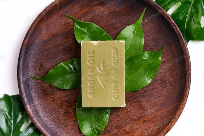 Bars of green natural olive oil soaps with green leaves on a wooden plate on white background, top
