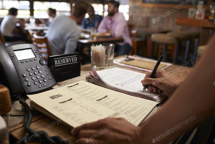 Mitarbeiter in einem Restaurant schreiben eine Tischreservierung