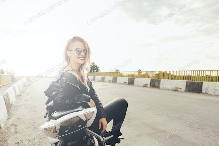 Schöne Frau posiert mit Sonnenbrille auf einem Motorrad