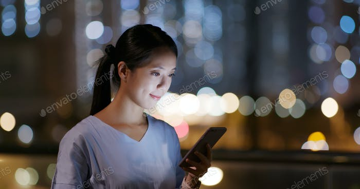 Woman look at the smart phone in city at night