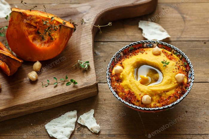 Pumpkin hummus and roasted butternut squash on background.