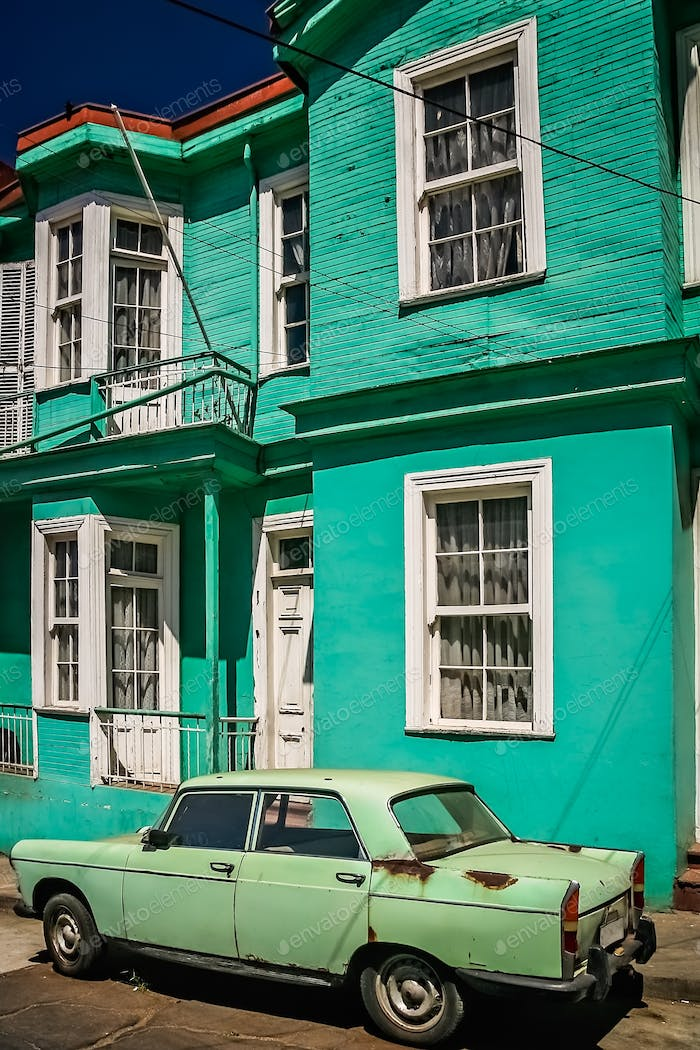 Old retro vintage green car in front of the old tenement house i