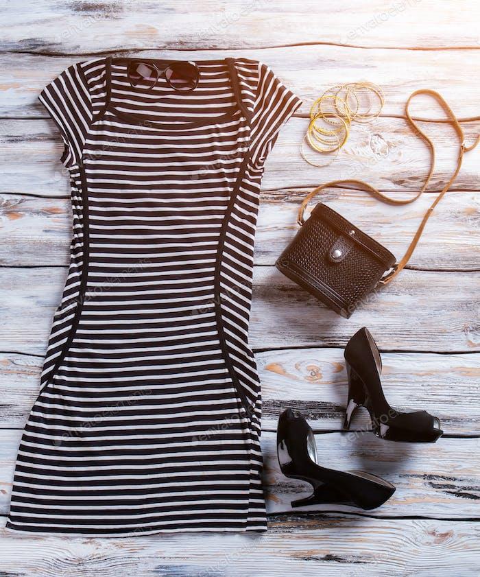 Gestreiftes Kleid und schwarze Geldbörse.