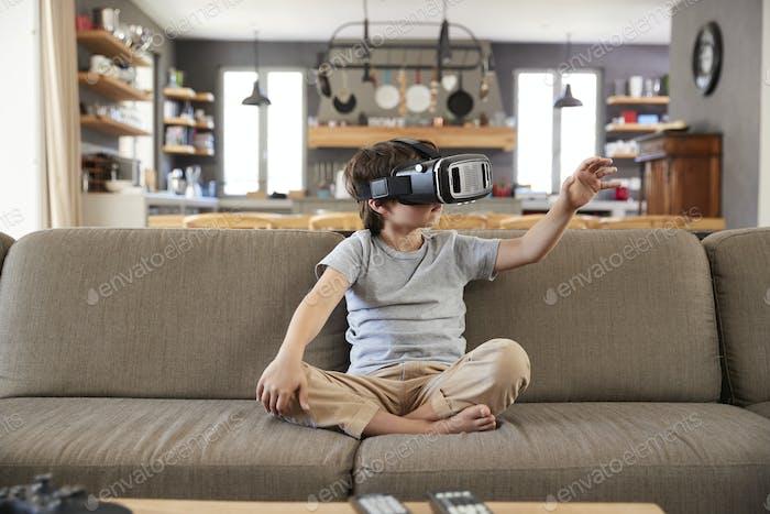 Boy Sitting On Sofa Wearing Virtual Reality Headset