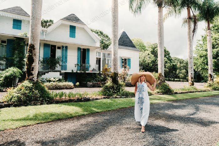 Junge schöne sexy Frau auf einer tropischen Insel. Stilvolles Mädchen in einem weißen langen Kleid und einem großen