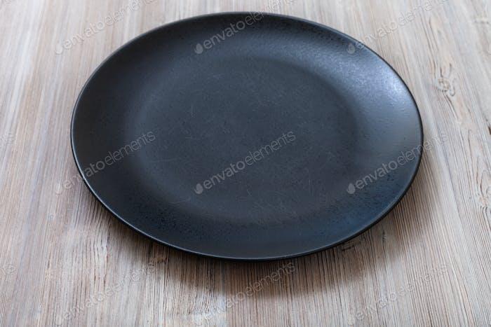 schwarze Platte auf graubraunem Tisch