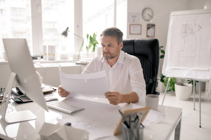 Mature serious architect in white shirt checking sketches by workplace