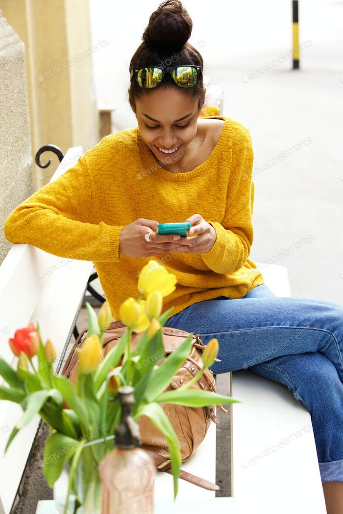 African woman on bench using cell phone