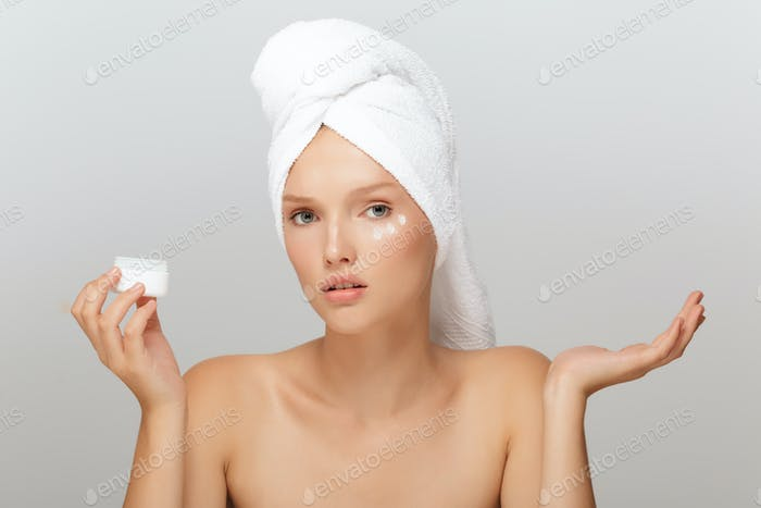 Portrait of young serious woman without makeup with white towel