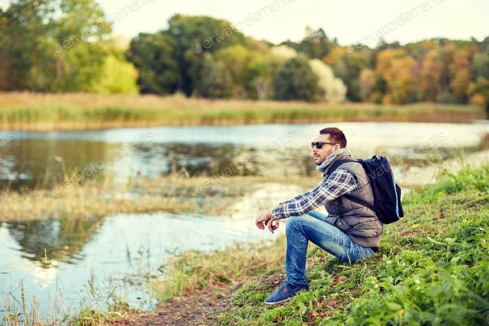 man with backpack resting on river bank