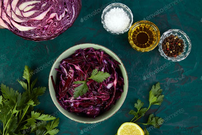 Shredded red cabbage in bowl on green background.