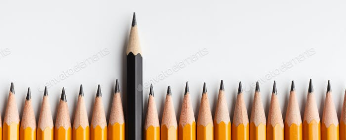 One black pencil protruding out of line with similar ones