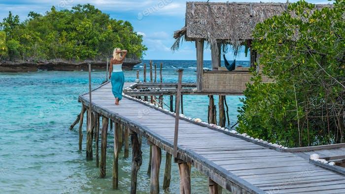Blond Mädchen Aufenthalt auf Holz Pier einer Homestay Blick in blauen Ozean, Gam Island, West Papuan