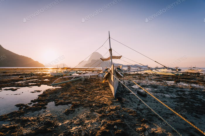 El Nido, Banca boat in low tide with beautiful sunset in background. Palawan island, Philippines
