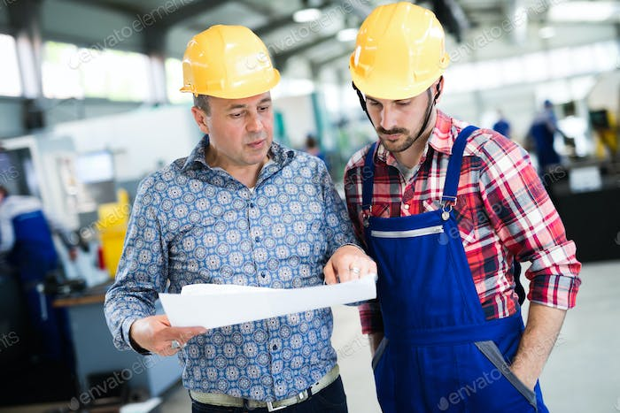 Supervisor and engineer working in metal industry