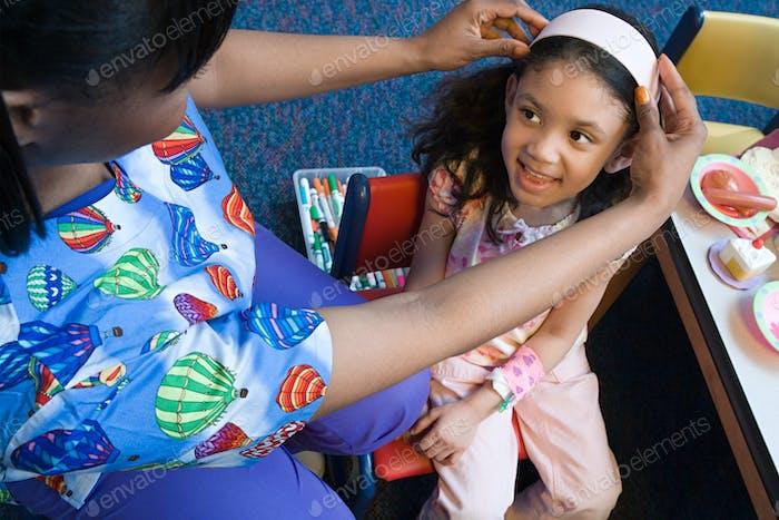 Krankenschwester setzen Stirnband auf Mädchen