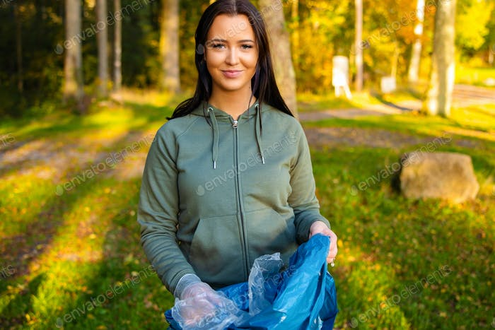 Young smiling female volunteer holding garbage bag at park