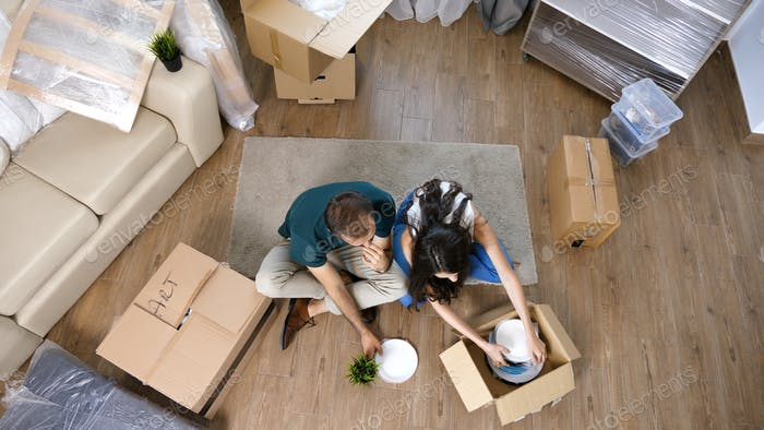 Young couple Moving in new home and unpacking carboard boxes.