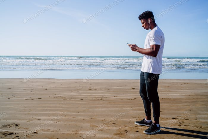 Athletic man using his mobile phone.