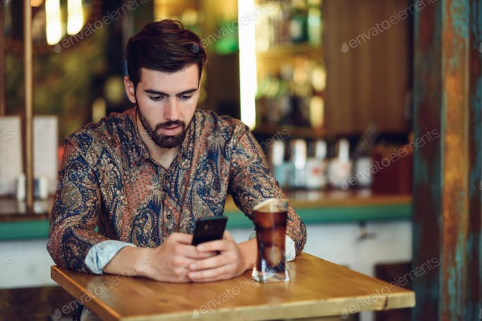 Young bearded man wearing casual clothes looking at his smartpho