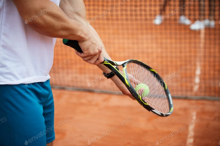 Tennis player prepares to serve ball during tennis match